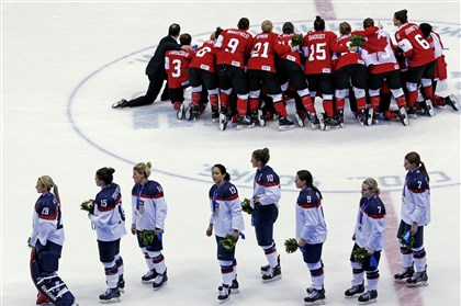 Sochi Olympics Ice Hockey Women Team USA skates off the ice with their silver medals as Team Canada poses for a photo with their gold medals in the women's gold medal ice hockey tournament Thursday at the Winter Olympics in Sochi, Russia.