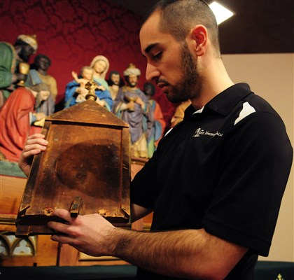 20140220CMCosmasWolf8450Mag Co-curator of the Saint Vincent Gallery Jordan Hainsey handles a reliquary from an altar depicting the Adoration of the Magi carved by Brother Cosmas Wol.