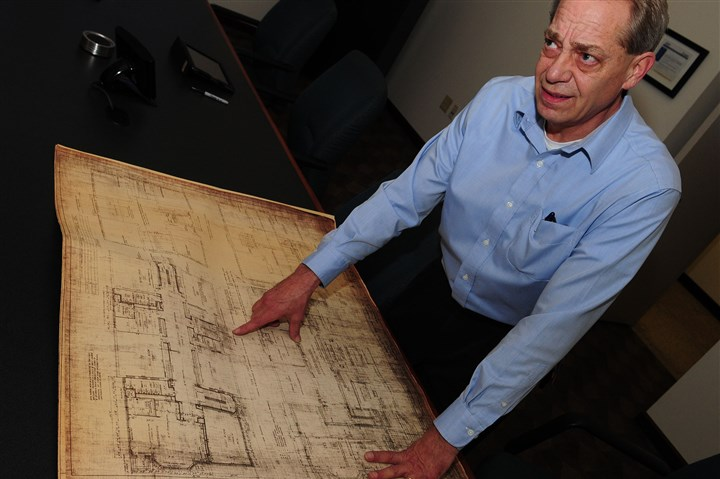 Dagostino Electronic Services Bob Dagostino, owner of Dagostino Electronic Services, lays out original floor plans of Hays Public School. In 2003, Mr. Dagostino's company repurposed the school, which had been unused and vacant for three decades.