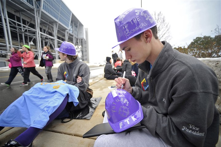 Penn State THON, waiting in line 01 Penn State student Michael Buchanan writes the name of a child on a hat he will be wearing as he sits in line for the Penn State IFC/Panhellenic Dance Marathon in University Park on Friday.