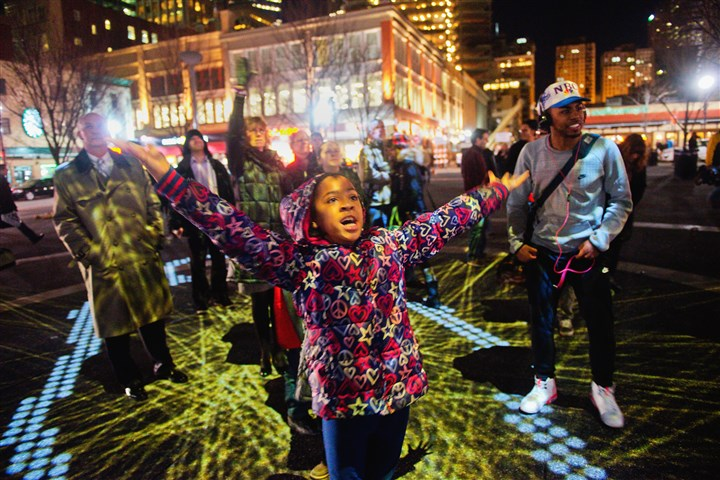 "'Congregation' in Market Square Amariya Bledsoe, 9, of Elliott at the art installation ""Congregation"" in Market Square on Friday. Lights are projected into the square and, as people interact with the lights, their interactions are projected on a screen."