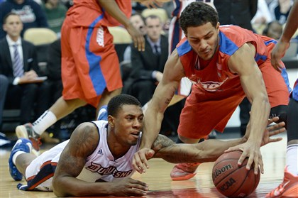 Duquesne's Ovie Soko vs Dayton Duquesne's Ovie Soko reaches for a loose ball against Dayton's Devin Oliver in the second half at Consol Energy Center Saturday afternoon.