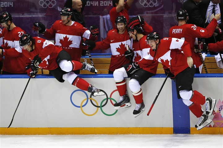 Canada hockey teams celebrates win The Canadian bench jumps out of the bench area to celebrate.