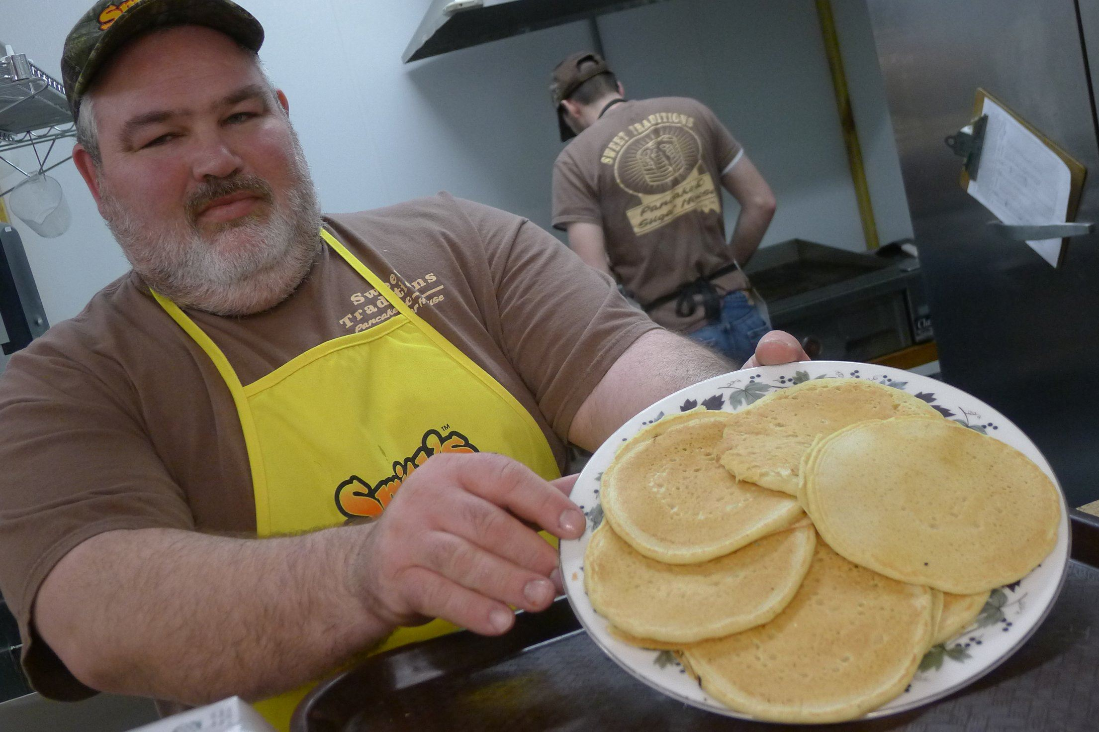 Sweet Traditions pancakes At Sweet Traditions near Corry in Erie County, Kerrie Clark's father, Drew Clark, holds up a plate of the all-you-can-eat pancakes.