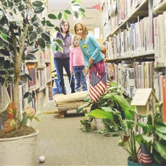 Library golf Danielle Deer, 9, putts through a hole with her sister Riley Deer, 6, and her mother Judy Deer of Richland, in the stacks of the Shaler North Hills Library.