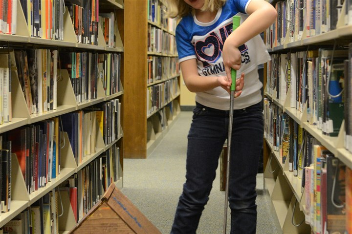 Library golf 2 Maggie Abt, 7, putts through an obstacle while playing golf with her grandmother Jan Watson in the stacks of the Shaler North Hills Library.