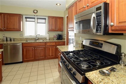 Condo on Shadow Ridge Drive, Harmar 3 The 12- by 9-foot kitchen has solid-wood cabinets and newer stainless steel appliances, creamy granite countertops and ceramic floor tile.