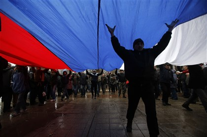 crimea1 Pro-Russian demonstrators march with a huge Russian flag during a protest Thursday in front of a government building in Simferopol, Crimea, which is an autonomous parliamentary republic within Ukraine.