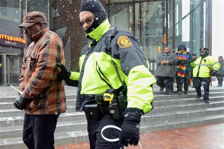 Arrest at UPMC protest Pittsburgh police lead 10 members of the Pa. Interfaith Impact Network from the U.S. Steel Tower, arresting them for trespassing after they demanded to speak with UPMC CEO Jeffrey Romoff. Over 100 gathered to protest UPMC workers' wages.