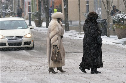 20140302snowstandalone07 Two women cross Penn Avenue perfectly clad for the falling snow and cold temperatures.