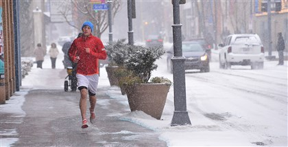 20140302lrsnowstandalone01 With bare legs Ben Mysliwiec makes his regular run from his home in the Strip District down Penn Avenue in the snow on Sunday.