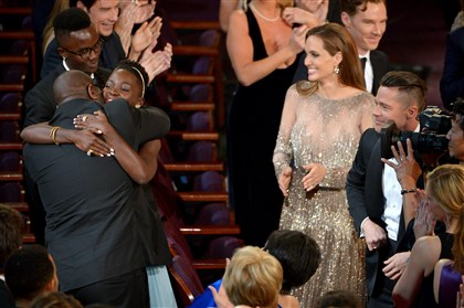 "86th Academy Awards Show ""12 Years a Slave"" Steve McQueen, left, and Lupita Nyong'o celebrate in the audience after ""12 Years a Slave"" is announced as winner of the award for best picture of the year during the Oscars at the Dolby Theatre on March 2, 2014, in Los Angeles."