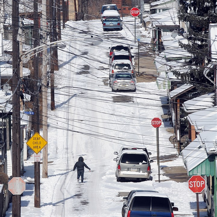 Snowy McKeesport street A pedestrian gingerly crosses snow-packed Soles Avenue in McKeesport Monday. Poor road conditions and lack of road salt caused the City of McKeesport to declare a state of emergency Monday morning.