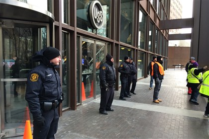 Police stand at the entrance to the U.S. Steel Tower Police stand at the entrance to the U.S. Steel Tower as protesters march in the plaza, which houses UPMC headquarters.