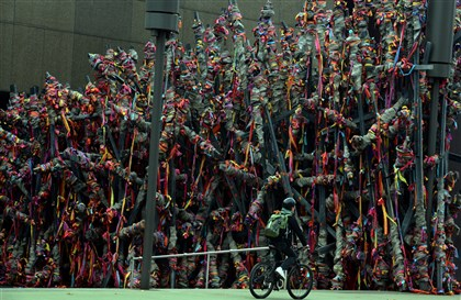 "20140305ppReviews_2-1 A cyclist rides past ""Tip"" on display in front of the Carnegie Museum of Art. The work by artist Phyllida Barlow, of London England, is part of the Carnegie International 2013."
