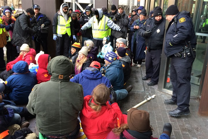 Protesters sit in front of the entrance to the U.S. Steel Tower Protesters sit at the entrance of the U.S. Steel Tower and UPMC offices on Tuesday while Pittsburgh police officers guard the revolving doors.
