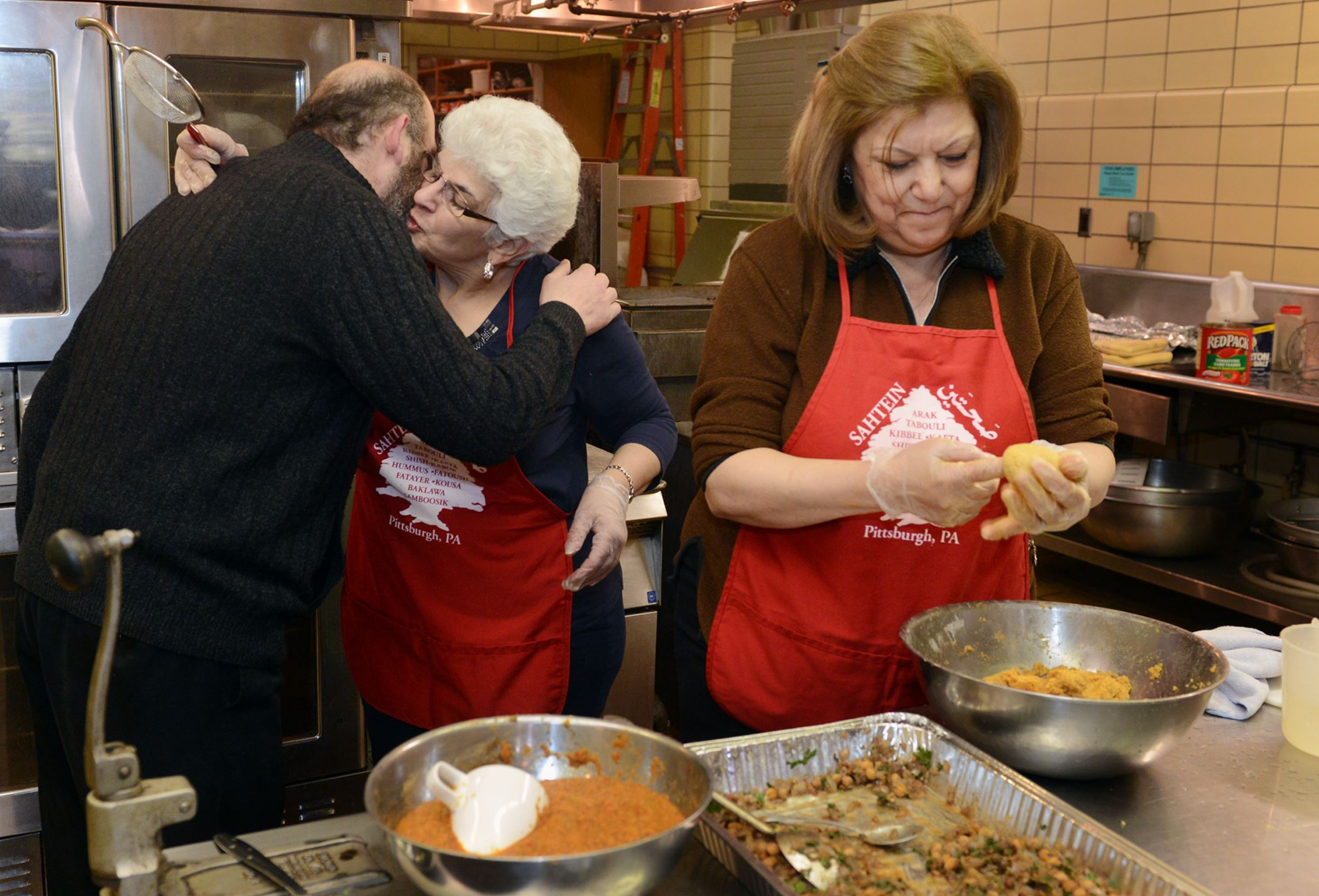 20140301bwCookFood04 Father Rodolph Wakim greets Anne Ayoob, of Pleasant Hills, center, who is helping Nellie Abdulnour of Brookline make pumpkin kibee at Our Lady of Victory Maronite Catholic Church in Scott Township.