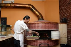 Ross McGarry, a pizziola at Piccolo Forno, roasts brussel sprouts in the wood burning oven at Piccolo Forno in Lawrenceville.