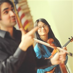 Fiddling Keira Wood, 13, looks on as fiddler Ryan Joseph applauds her improvisational skills during a workshop on fiddle playing for orchestra students at Moon Area Middle and High School. Mr. Joseph, a Grammy-nominated artist, introduced the students to the basic elements of fiddle playing.