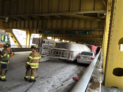 Truck wreck 2 Firefighters stand near the truck that overturned Wednesday morning on the outbound Fort Pitt Bridge.