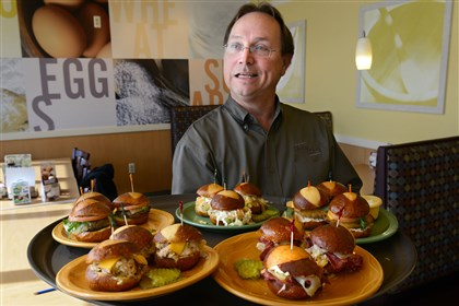 Chris Whalen, president of KCS Management, Chris Whalen, president of KCS Management, a holding company and operator of Kings Family Restaurant, holds a selection of pretzel roll sliders at the Kings in North Versailles.