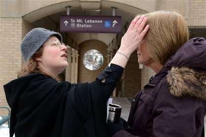 "Laura Wholey receives ashes The Rev. Michelle Boomgaard, of St. Paul's Episcopal Church in Mt. Lebanon, applies Ashes to Laura Wholey of Mt. Lebanon in front of the Mt. Lebanon ""T"" station along Washington Road. Ms. Wholey was on her way to work."