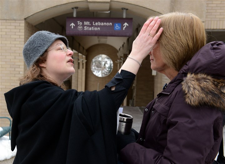 20140305dsAshesLocal01 The Rev. Michelle Boomgaard of St. Paul's Episcopal Church in Mt. Lebanon applies ashes March 5 to Laura Wholey of Mt. Lebanon in front of the Mt. Lebanon T Station along Washington Road.
