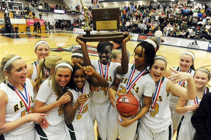 Seton-LaSalle girls Yacine Diop hoists the WPIAL Class AA girls basketball trophy and teammate Naje Gibson displays the game ball as the Seton-LaSalle girls celebrate their championship earlier this month.