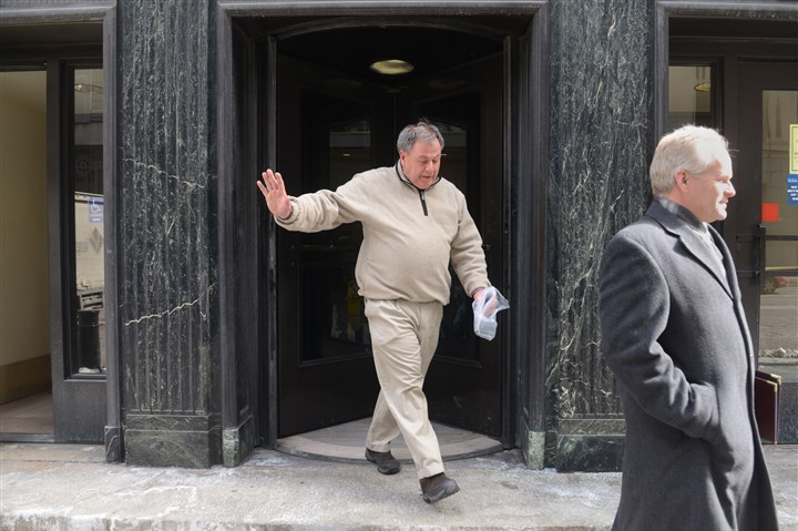 20140305_Mangis03-1 Air National Guard Colonel Gerard Mangis waves to a TV reporter as he exits the U.S. Federal Courthouse along with his lawyer Charles Porter, Jr., right, after being indicted on 110 counts.