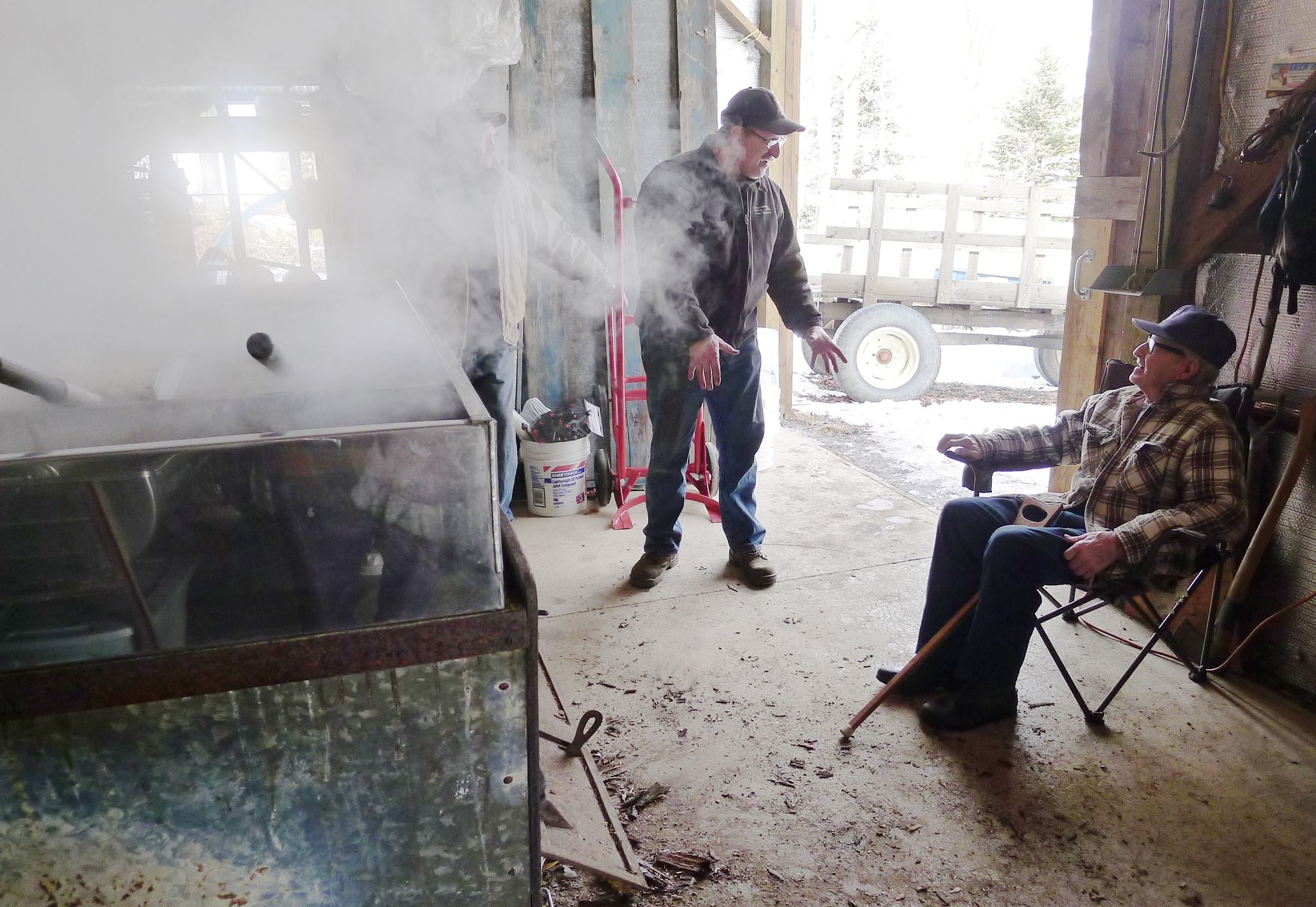 20140224hobbmaple1food In the steamy sugarhouse at Sweet Traditions near Corry, Erie County, John Wiggers Sr., seated at right, talks with neighbor Steve Anderson, standing, and son-in-law Joe Catalfu, standing in the steam behind him, while they all watch Mr. Wiggers' grandson Casey Catalfu boiling the season's first maple sap.