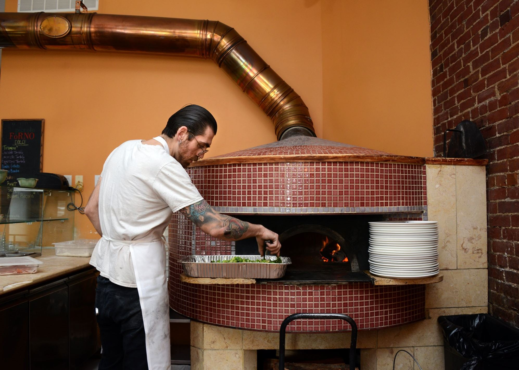 201435RARmagoven2-1 Ross McGarry, a pizziola at Piccolo Forno, roasts Brussels sprouts in the wood burning oven at the Lawrenceville restaurant.