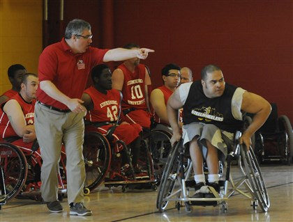 Edinboro University coach Jim Glatch  Edinboro University coach Jim Glatch yells to his team as Steelwheelers player Lincoln Jamison, right, passes by. Edinboro's wheelchair basketball program is one of seven men's and five women's college programs in the country.