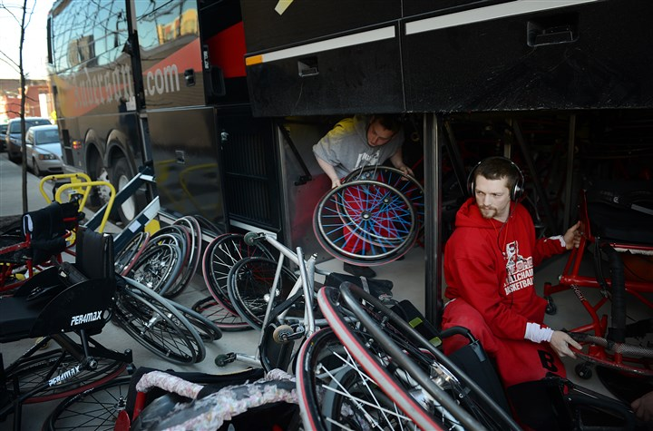 Edinboro University wheelchair basketball team's bus Derek Strickland, 31, of Suffolk, Va., far right, helps to unload the Edinboro University wheelchair basketball team's bus before a February game against the Pittsburgh Steelwheelers at the Thelma Lovette YMCA in the Hill District.
