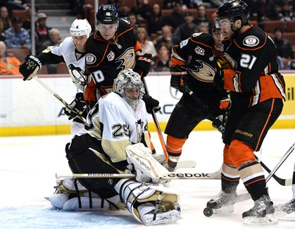 20140308WP_penguinswin Marc-Andre Fleury makes a save as the Ducks' Corey Perry and Kyle Palmieri look for a rebound Friday in Anaheim.