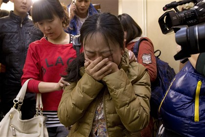 China Malaysia Plane A Chinese relative of passengers aboard a missing Malaysia Airlines plane cries as she leaves a Beijing hotel room for relatives or friends of passengers aboard the missing airplane.