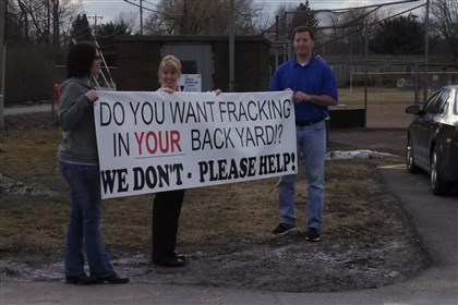 Protesters against drilling People hold a sign protesting a plan to drill under Mars Area School District schools.