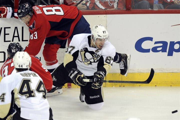 Penguins Capitals Hockey Penguins center Sidney Crosby goes for the puck against Washington Capitals center Jay Beagle during the third period last night.