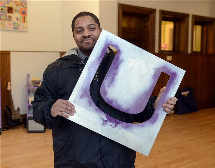 "20140305bwArtMag03  Brandon McMillan of West Mifflin returns his borrowed art piece, ""U Stencil for Art Lending Collection, Braddock Library, 2013"" by Wade Guyton."