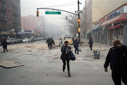APTOPIX NYC Explosion People run after an explosion and building collapse in the East Harlem neighborhood of New York, Wednesday. The explosion leveled an apartment building, and sent flames and billowing black smoke above the skyline.