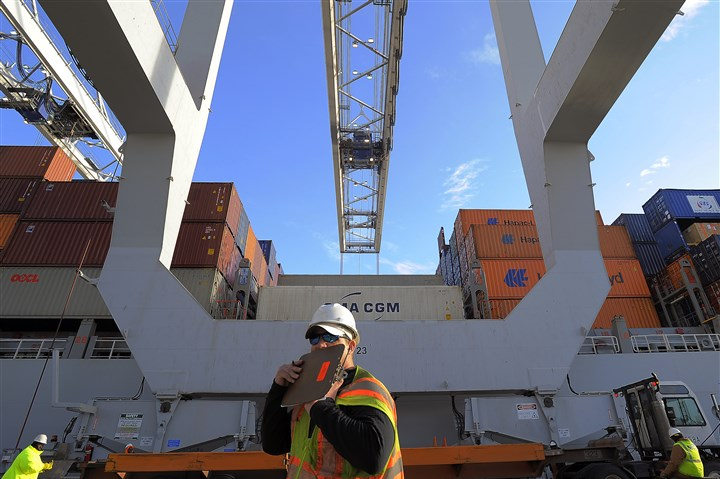 Wholesale Trade Inventories In this Monday, Jan. 2, 2014, photo, a dock worker communicates on a walkie-talkie while a ship to shore crane loads containers onto a ship at the Georgia Ports Authority Garden City terminal, in Savannah, Ga. The Commerce Department releases wholesale trade inventories for January on Tuesday, March 11, 2014. (AP Photo/Stephen B. Morton)