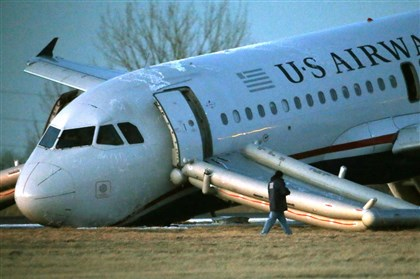 20140313usair A person walks around a damaged US Airways jet at the end of a runway at the Philadelphia International Airport.