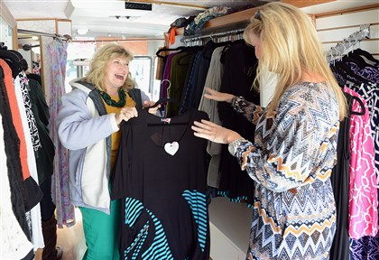 StyleTruck2013 Jackee Ging, right, helps customer Pam Palmer choose a dress in Ms. Ging's Style Truck fashion van in Downtown's Market Square in September.