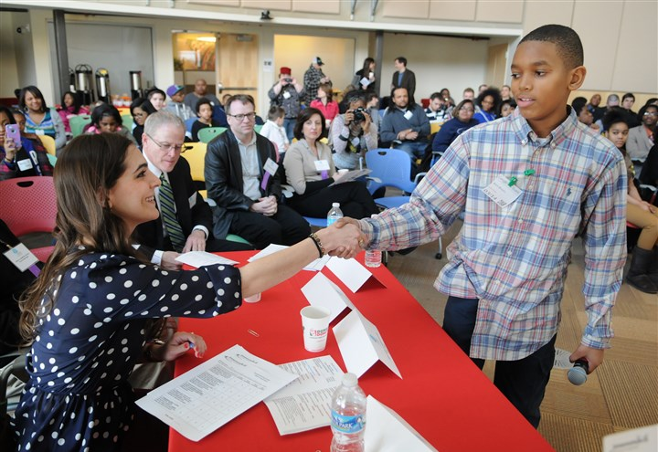 20140315EntrepeneuringYouth-2 Amir Brooks, 11, of Beaver Falls shakes hands with Sara Longo, co-founder and COO of Share Closet, at the iPitch Competition at the Google offices in Bakery Square on Saturday.