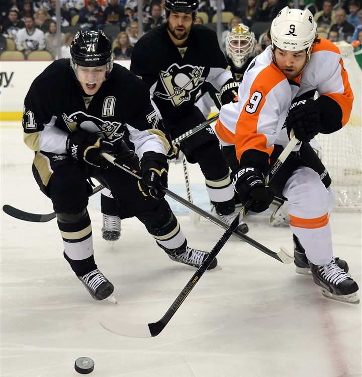 Evgeni Malkin vs. Steve Downie The Penguins' Evgeni Malkin fights for the puck against the Flyers' Steve Downie in the second period.