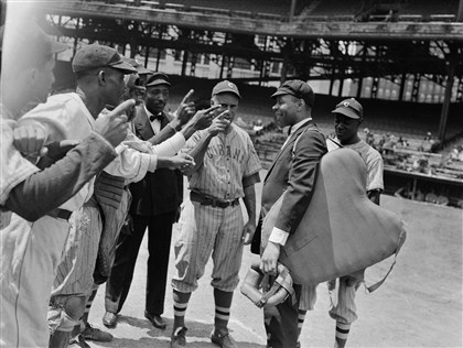 "New York Cubans players and a Homestead Grays player  New York Cubans players and a Homestead Grays player ""argue"" with umpire Bill Harris at Forbes Field in 1941. Harris' smile suggests this is a posed photo."