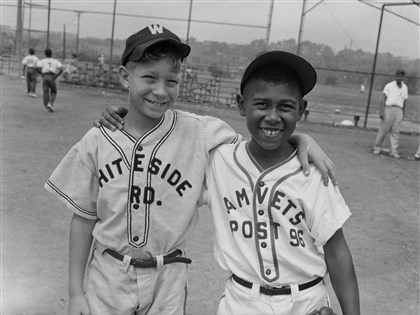 Two young baseball players standing on a ballfield Two young baseball players standing on a ballfield, possibly in the Hill District c. 1953-1956. Gary Henderson, right, wears an Amvets Post 96 uniform. The other boy, whose name is not known, wears a uniform from Whiteside Road, one of Pittsburgh's first public housing projects. It opened in the early 1950s and was razed in 2002.