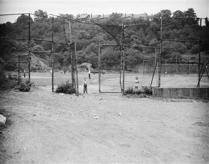 Children standing by a sandlot baseball diamond 