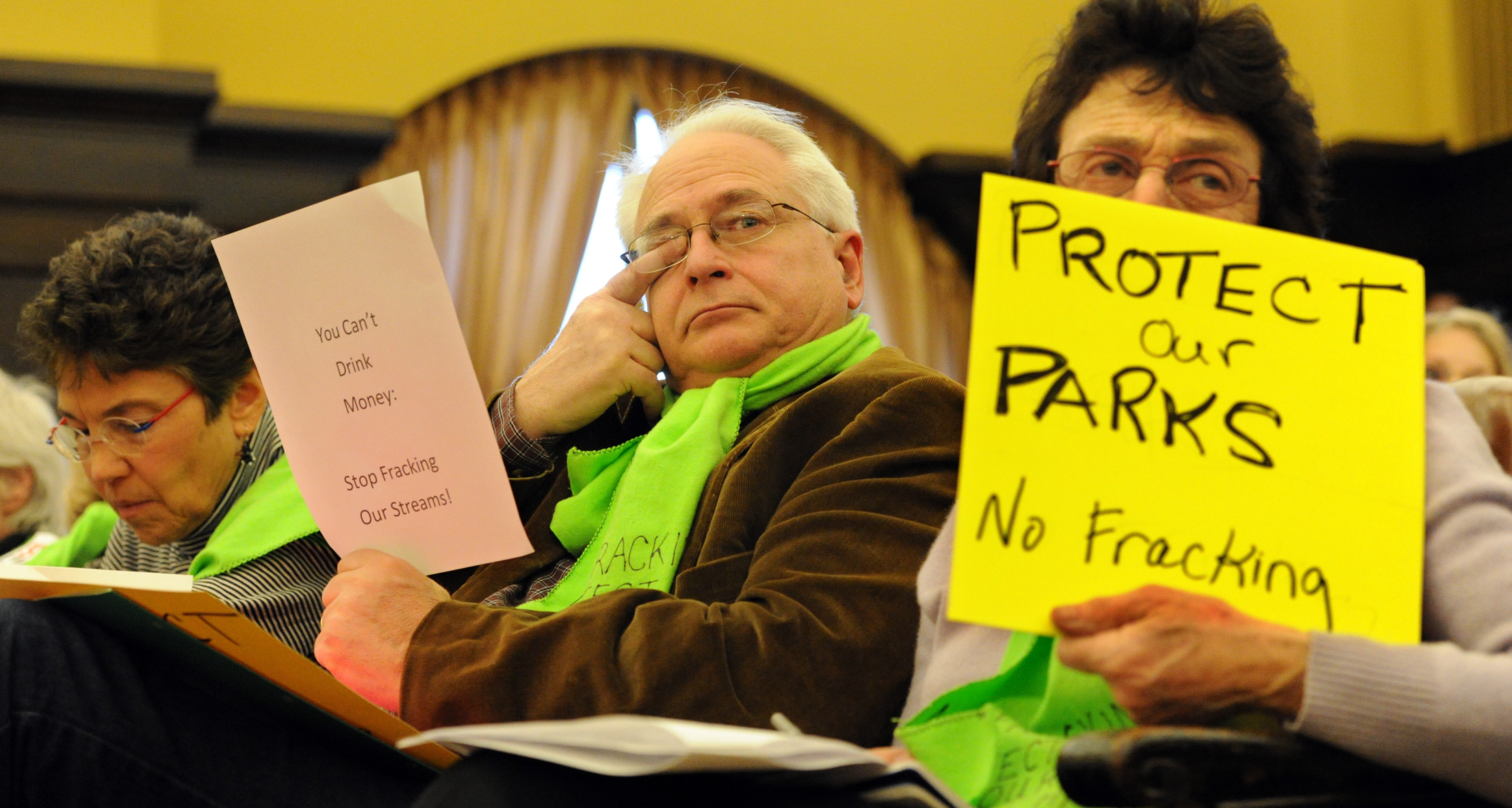 20140318JHLocalDrill01 Michael Simms, left, and Joni Rabinowitz, right, listen to county Executive Rich Fitzgerald talk about the agreement reached for drilling for natural gas under Deer Lakes Park. The protesters were at Tuesday's county council meeting.