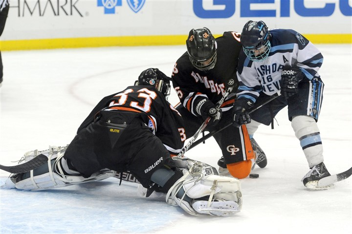 Photographer Bishop Canevin's Randy Unger digs for the puck as Cathedral Prep goaltender Grant Kennedy and teammate Anthony Piglowski defend during the Class AA Penguins Cup championship maych Monday at Consol Energy Center.