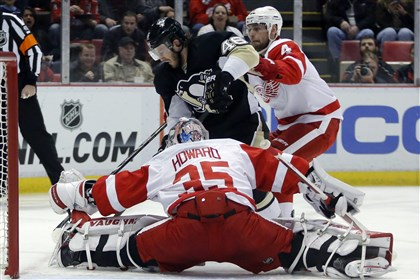 Penguins Red Wings Hockey.J Red Wings goalie Jimmy Howard stops a shot by Penguins defenseman Deryk Engelland as Red Wings' Jakub Kindl helps defend the goal during the first period in Detroit.